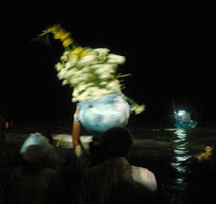 Imagem do ensaio Corpos e flores para Iemanjá, do fotógrafo Paulo Rossi, realizado na Praia de Tambaú, João Pessoa - PB. Na foto, os fieis são registrados, de costas, à madrugada, caminhando em diração ao mar, e levando sobre a cabeça um barco azul, enfeitado com flores, fitas e outros adereços, uma oferenda à Iemanjá, orixá das religiões de origem africana, rainha dos mares, padroeira dos pescadores e barqueiros.